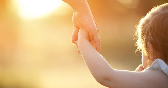 Toddler holding hands with mother