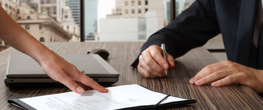 hand pointing to contract document on table