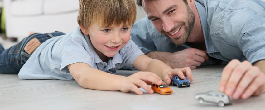 Father with son playing with toy cars