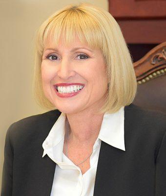 Ann Marie Gilden smiling, sitting in desk chair